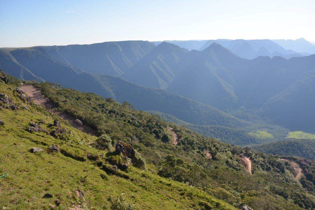 """Espigão da Serra Velha, desde o topo com a Matinha Nebular-Caminho dos Conventos 1728-1730 (Esquerda acima e o """"facão"""", espigão de subida do Pioneiro Caminho de Tropas pelo Interior. Visto do Mirante de Vôo –borda da Serra-Estrada da Rocinha. Visão para o N. 1245 m de alt.. Estrada –Passo da Rocinha –""""Caracóis da Estrada Velha"""" da Rocinha BR-285--interditada atualmente - em obras de pavimentação."""