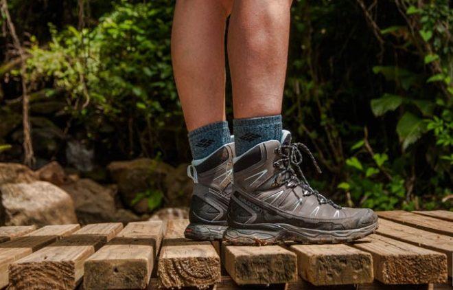 Para cégo ver: A imagem foca nos pés de uma pessoa que está calçando uma bota Salomon, enquanto está parada sob uma ponte de madeira. Ao fundo, rochas e plantas verdes aparecem de segundo plano.