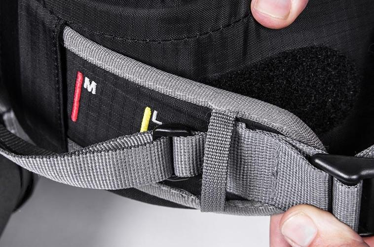 Para cégo ver: A imagem ilustra a regulagem da barrigueira de uma mochila preta.
