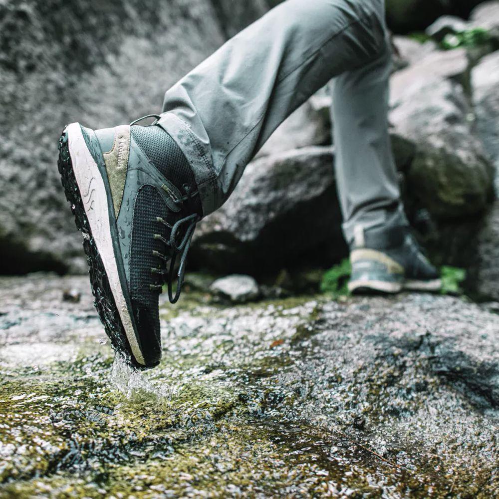 Para cégo ver: A imagem foca nos pés de uma pessoa que está caminhando com uma bota da Columbia em um terreno rochoso e molhado.