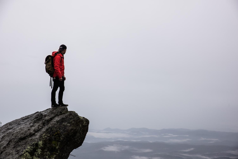 Para cégo ver: A imagem mostra um homem, vestindo uma jaqueta vermelha e um boné. Ele está com uma mochila de ataque nas costas, parado na ponta de uma pedra, observando uma paisagem que está com clima fechado e com bastante nuvem no céu.