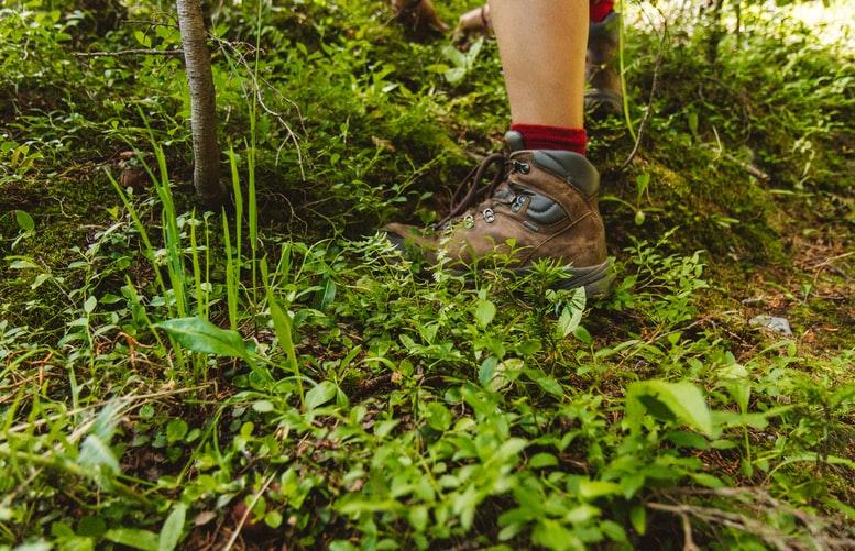 Para cégo ver: A imagem foca nos pés de uma pessoa que está calçando uma bota marrom e está pisando em uma trilha com alguns matos rasteiros.