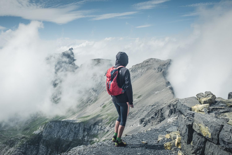Para cégo ver: A imagem mostra uma pessoa, com jaqueta, capuz na cabeça e uma mochila nas costas, caminhando em uma montanha rochosa encoberta por uma névoa.