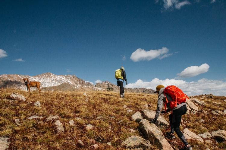 Para cégo ver: A imagem mostra duas pessoas caminhando em uma região montanhosa, ambos com mochila de ataque nas costas, enquanto um cachorro os acompanha..