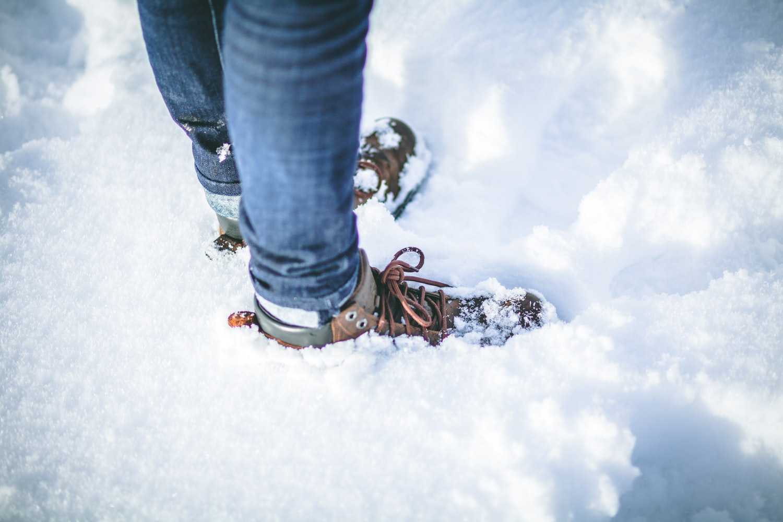 Para cégo ver: A imagem foca nos pés de uma pessoa que está calçando uma bota marrom, enquanto está parada com os pés afundados na neve.