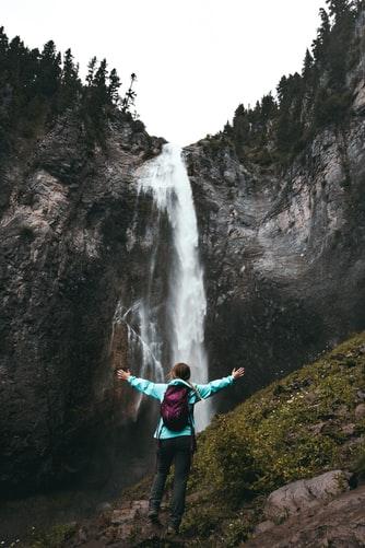 Para cégo ver: A imagem mostra uma mulher de costas, com os braços abertos e com uma mochila nas costas, observando uma cachoeira.