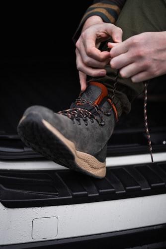 Para cégo ver: A imagem mostra uma bota Columbia calçada no pé de uma pessoa que está a amarrando. Ela está com o pé apoiado no parachoque traseiro de um carro.
