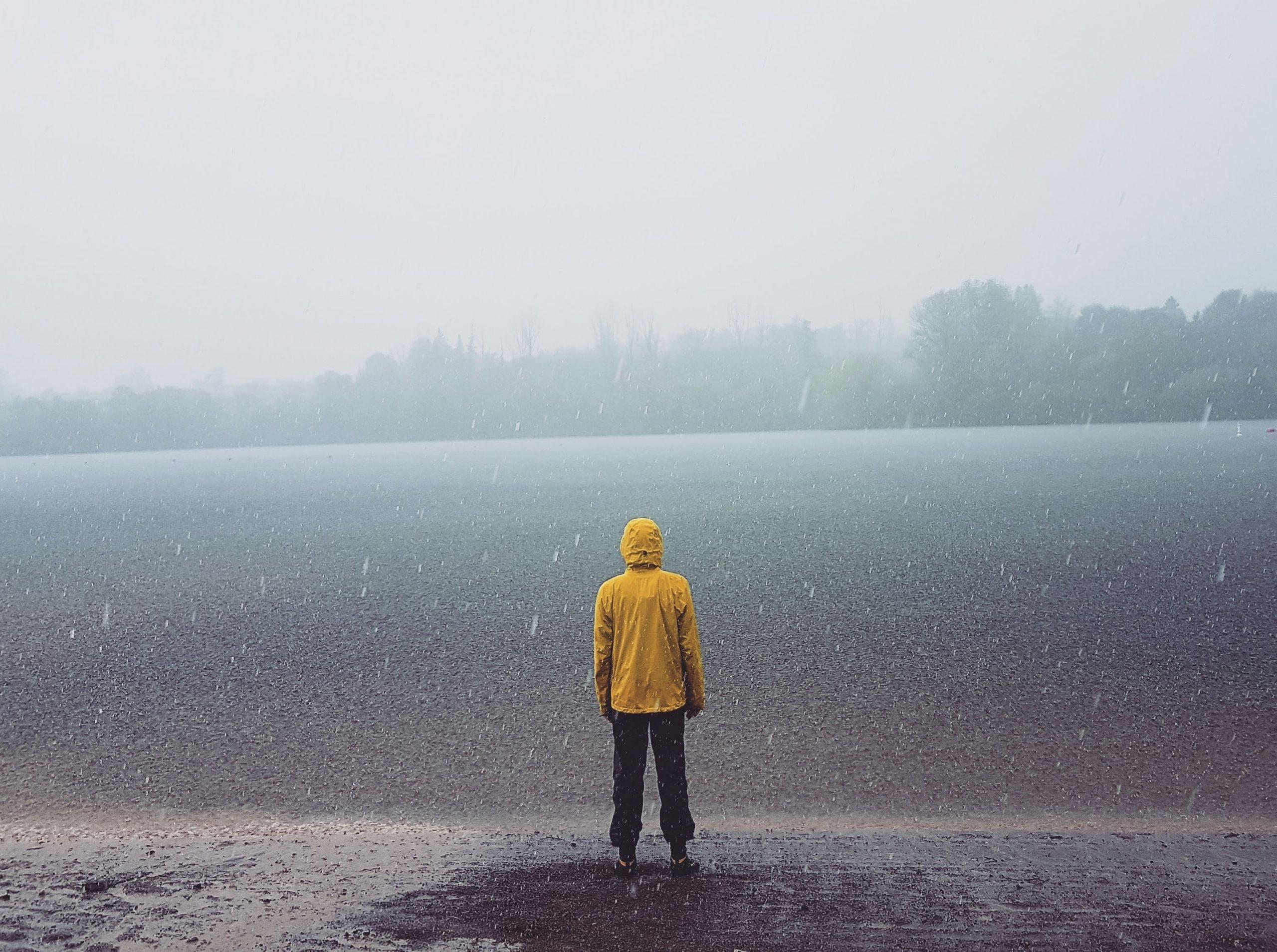 Para cégo ver: A foto insaturada exibe um homem de costas parado sob a chuva, com jaqueta impermeável amarela observando um campo liso, de grama baixa. Mais ao fundo é possível notar algumas árvores.