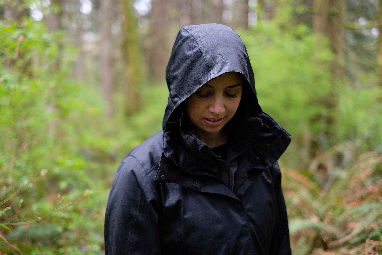 Para cégo ver: A foto mostra uma mulher vestida com uma jaqueta impermeável preta, olhando para baixo. Ao fundo aparece uma floresta desfocada.