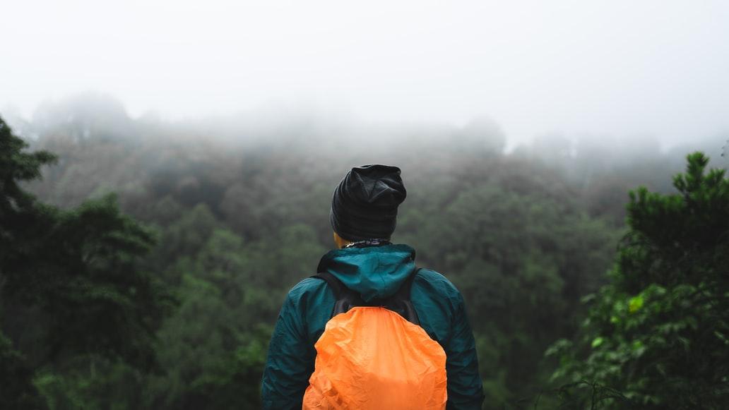 Para cégo ver: Um homem com touca, jaqueta impermeável e mochila com capa de chuva observa de costas para a câmera a vastidão da paisagem que contem muitas árvores, em desfoque. É possível notar as nuvens cobrindo a copa de algumas árvores.