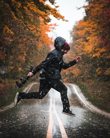 Para cégo ver: Um homem de jaqueta impermeável preta atravessa correndo e pulando a estrada sob a chuva, com sua câmera fotográfica em mãos. O fundo desfocado apresenta uma floresta de árvores altas com as folhas amareladas pelo outono, beirando a estrada.